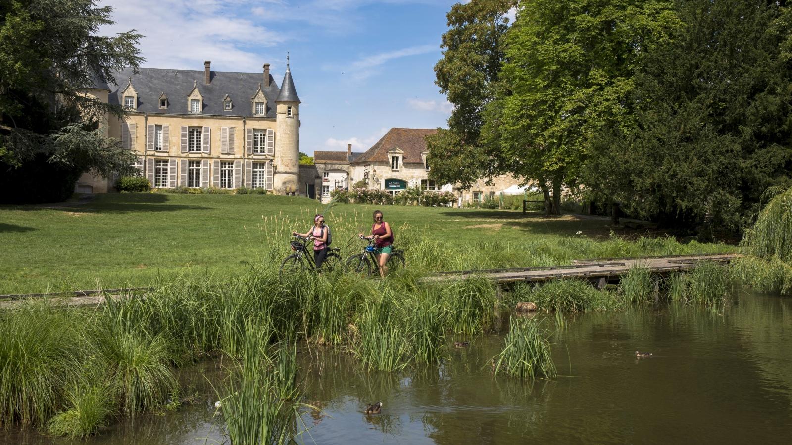 Photo de deux cyclistes en balade dans le parc de la Maison du Parc du PNR Vexin français à Théméricourt, Val-d'Oise (95). On y aperçoit le château de la Maison du Parc en fond, et en premier plan une randonnée à vélo.