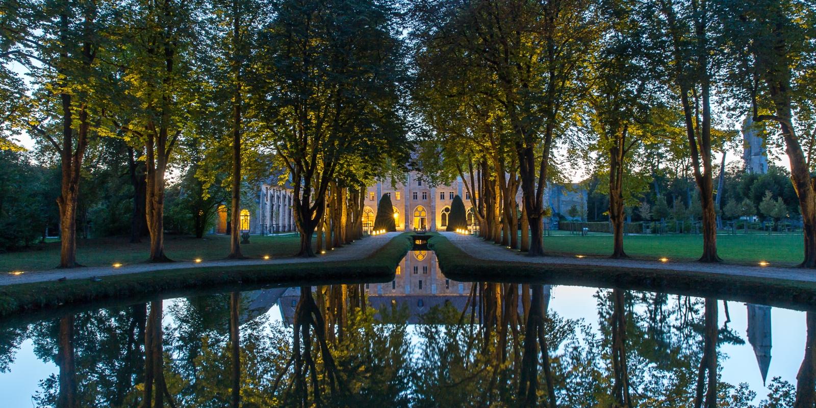 Photo prise de nuit du parc de l'abbaye de Royaumont avec l'abbaye éclairé au fond dans la trajectoire de l'eau du petit bassin du parc
