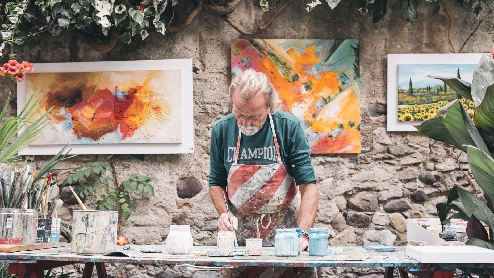 Photo d'un homme peignant dans sa cours avec des tableaux affichés en arrière plan. Illustration du courant impressionnisme à Auvers-sur-Oise.