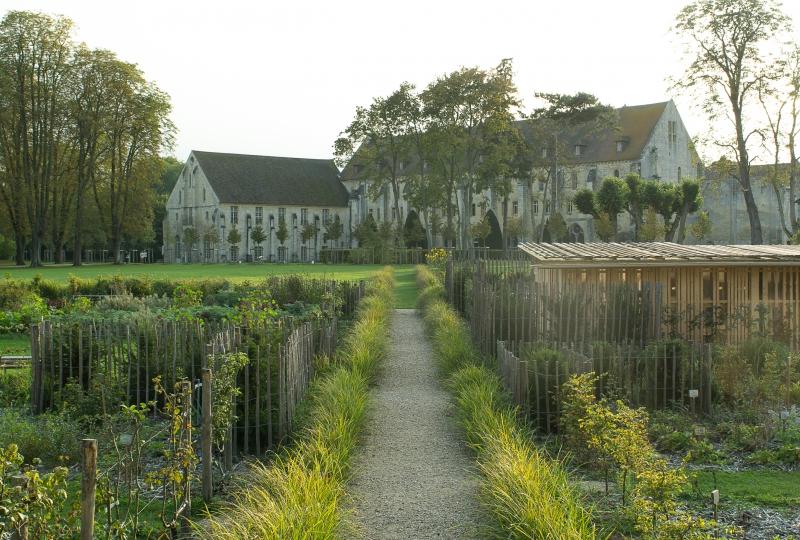 Photo du potager de l'abbaye de Royaumont avec un chemin et le bâtiment en arrière plan