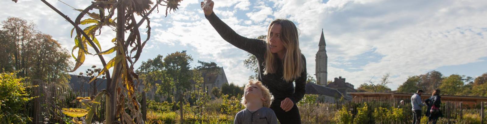 Photo d'une maman et son fils au potager de l'abbaye découvrant au soleil les espèces de plantes du potager