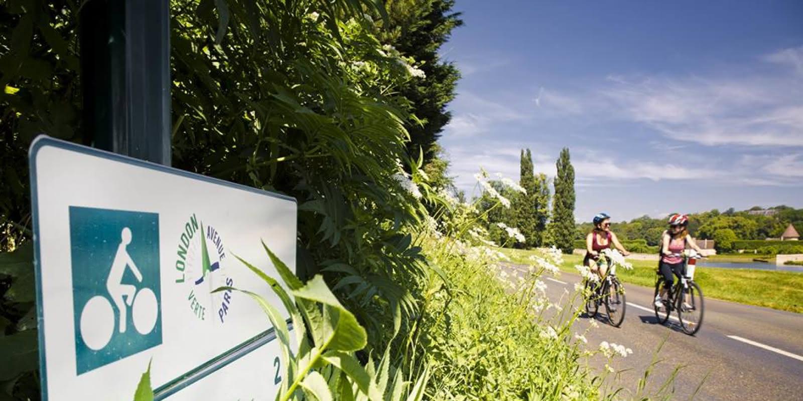 Photo de deux femmes faisant du vélo revenant de Gisors et passant près d'un panneau de signalisation Avenue Vert London-Paris
