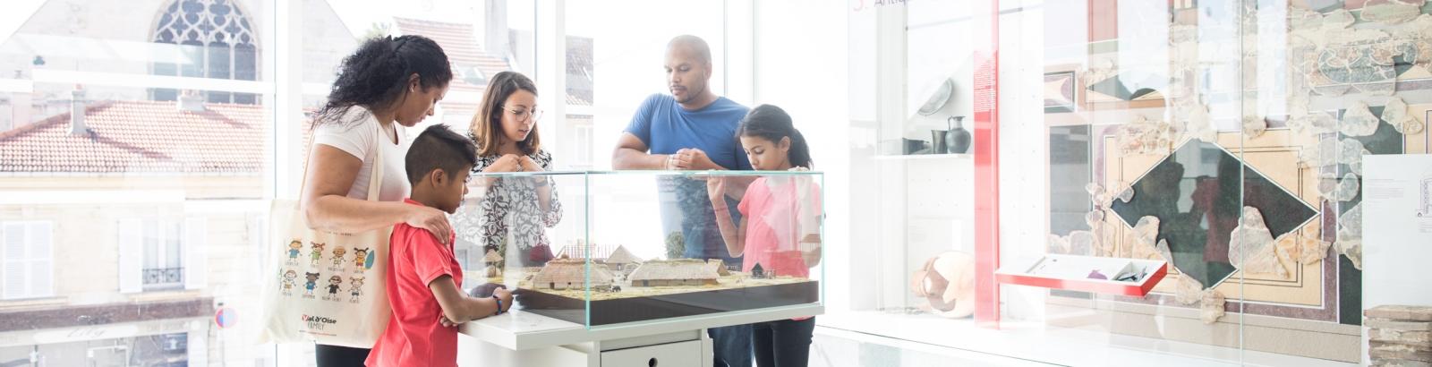 Photo d'une famille au musée Archéa à Louvres avec une guide de musée qui explique ce qu'il y a en vitrine