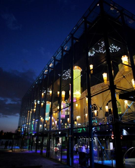 Photo extérieur du casino d'Enghien prise de nuit avec ses façades vitrées illuminées à l'intérieur par ses lumières au bord du lac