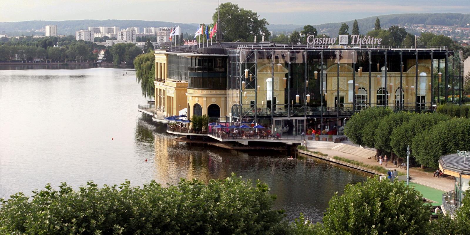 Photo du paysage avec le casino théâtre à moitié vitré et vue sur le reste de la ville et le lac