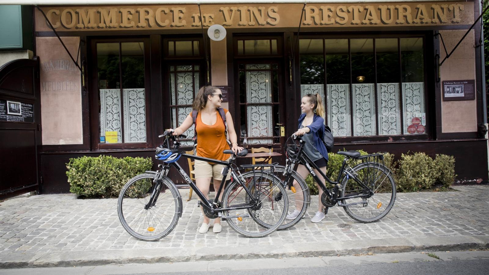Photos de deux femmes avec leur vélo en face de l'auberge Ravoux où vécut Vincent Van Gogh à Auvers-sur-Oise