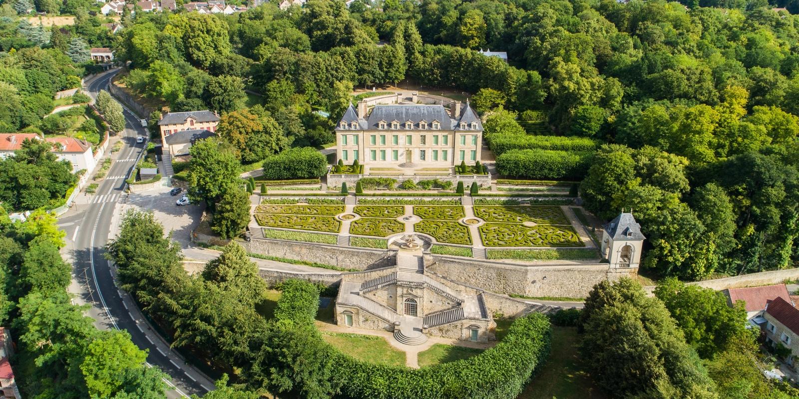 Photo du Château d'Auvers son jardin à la française et ses alentours prise en drône depuis le ciel