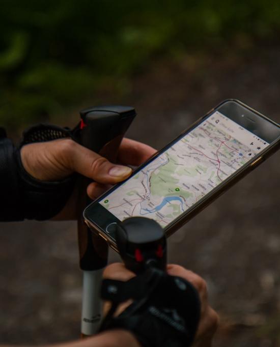 Photo d'un homme avec des bâtons de marche regarde une carte interactive sur son téléphone portable dans un chemin forestier