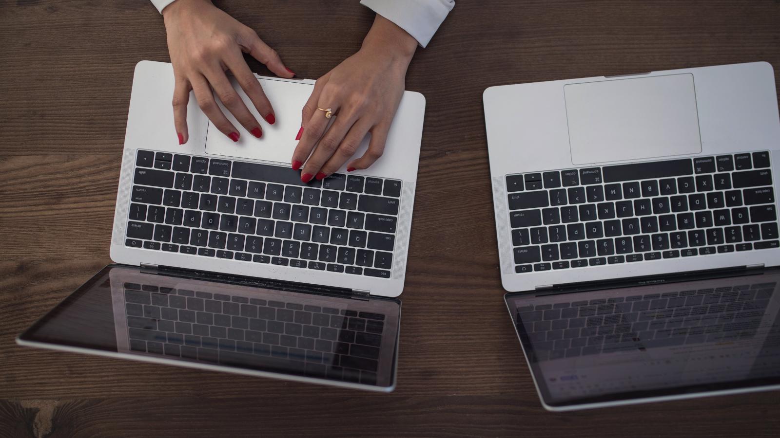 Photo de mains féminines utilisant un ordinateur près d'un autre ordinateur également ouvert