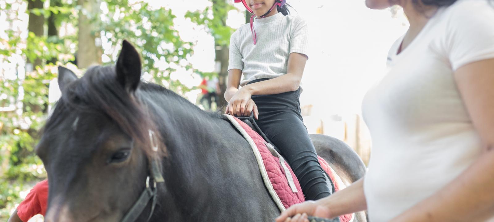 Photo d'une petite fille sur un poney avec sa maman qui tient la bride au parc Sherwood Parc à Viarmes dans le Val d'Oise