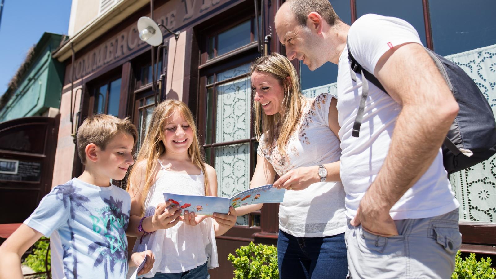 Photo d'une famille à Auvers-sur-Oise faisant un parcours de visite dans la ville à l'aide d'un guide papier