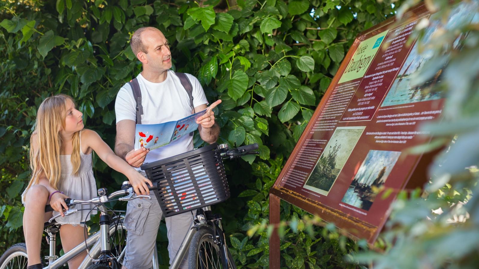 Photo d'un père et sa fille à vélo se renseignant sur un panneau du musée de Daubigny à Auvers-sur-Oise