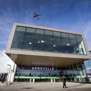 Photo de l'extérieur du centre commercial d'aéroville avec un avion qui passe au dessus dans le ciel bleu