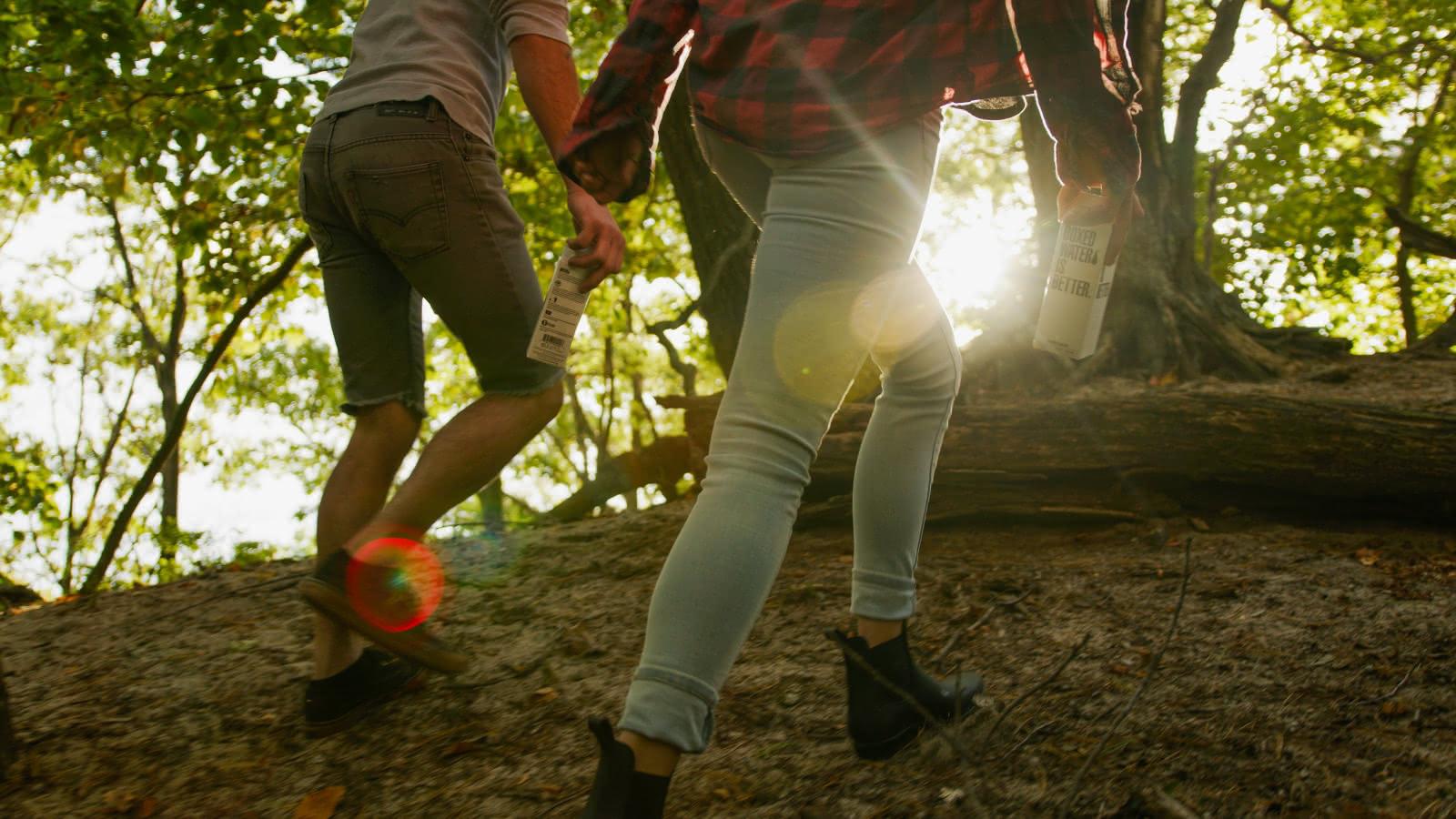 Photo de deux jeunes gens en promenade dans la forêt avec les rayons du soleil