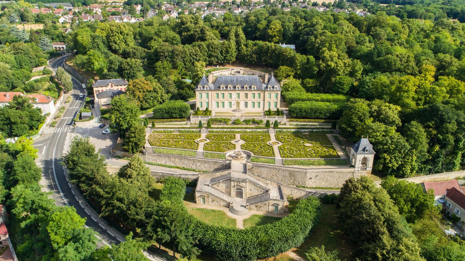 Photo du château d'Auvers et de ses jardins vu de drône avec beaucoup d'arbres et quelques habitations autour