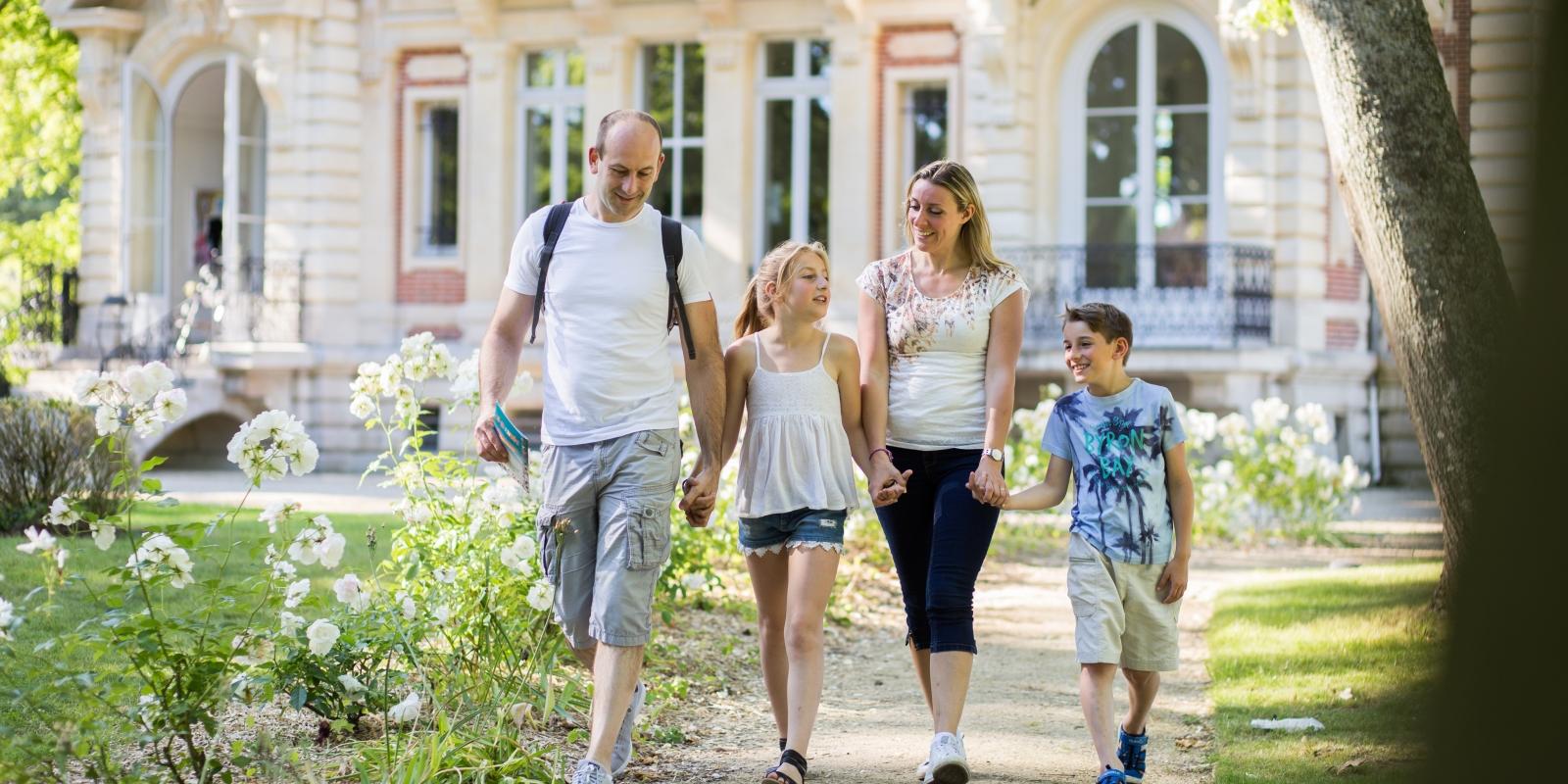 Photo d'une famille main dans la main en promenade à l'Isle Adam devant le musée Senlecq