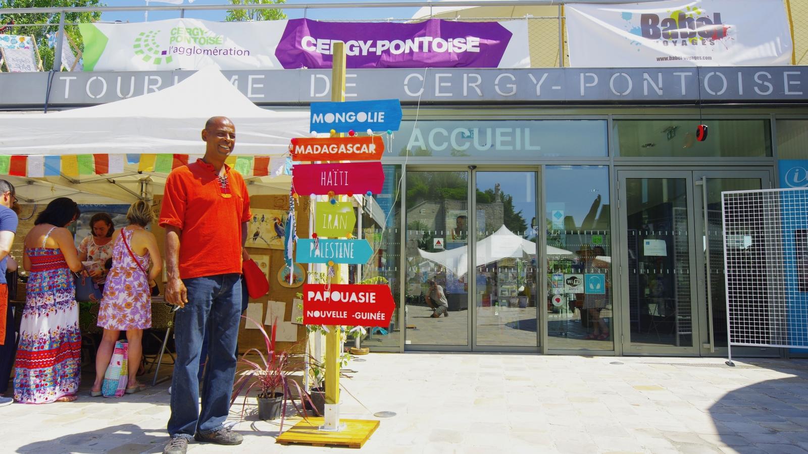 Photo d'un homme et de pancartes prise devant l'office de tourisme de Cergy-Pontoise en 2017 lors du No Mad Festival sur la thématique Haïti
