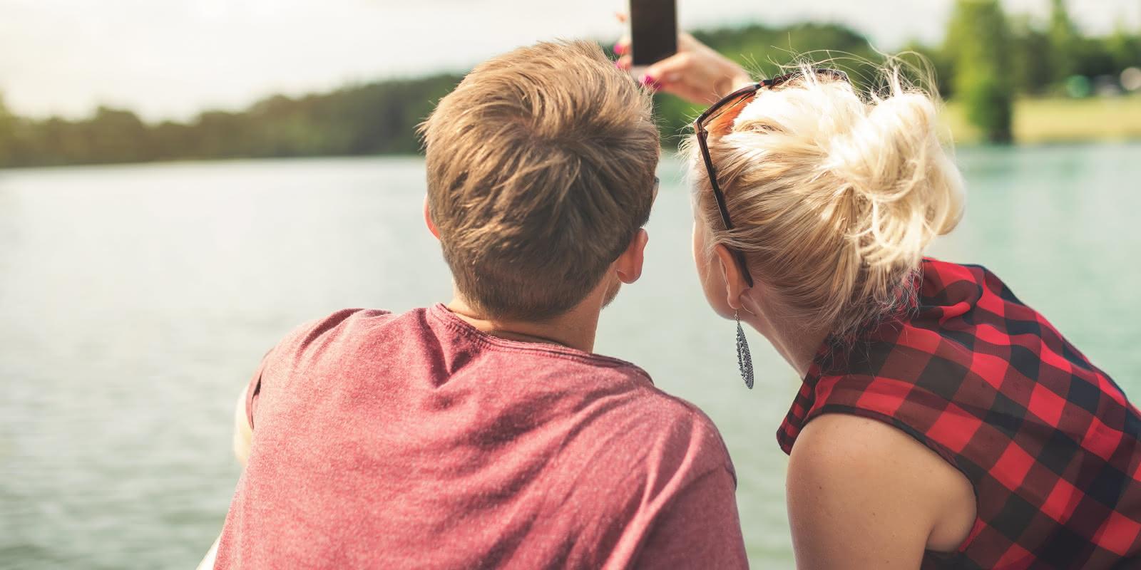 Photo d'un couple se prenant en photo selfie avec un téléphone portable sur le ponton d'un lac