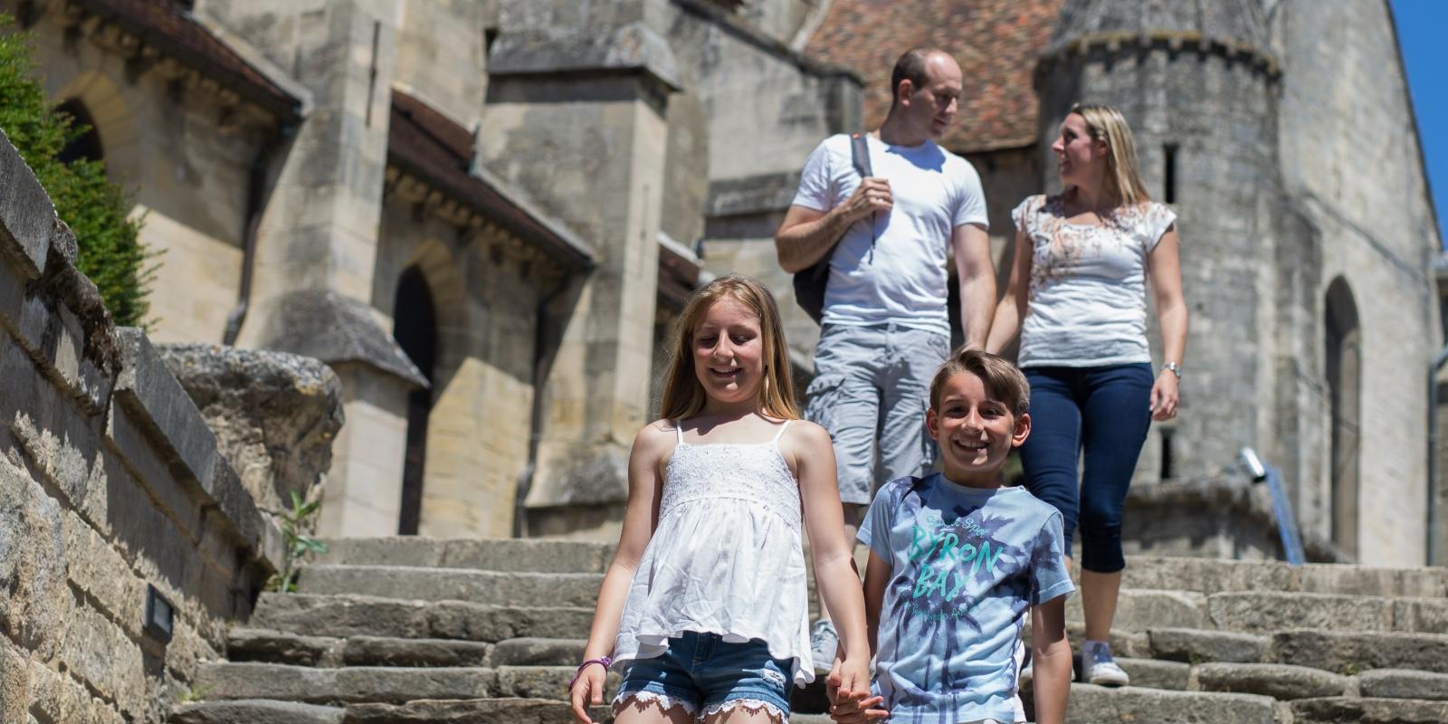 Photo d'une famille souriante avec deux enfants et leurs parents se tenant la main en descendant les marches près de la célèbre église d'Auvers sur Oise peinte par Vincent Van Gogh dans le Val d'Oise sous un beau ciel bleu