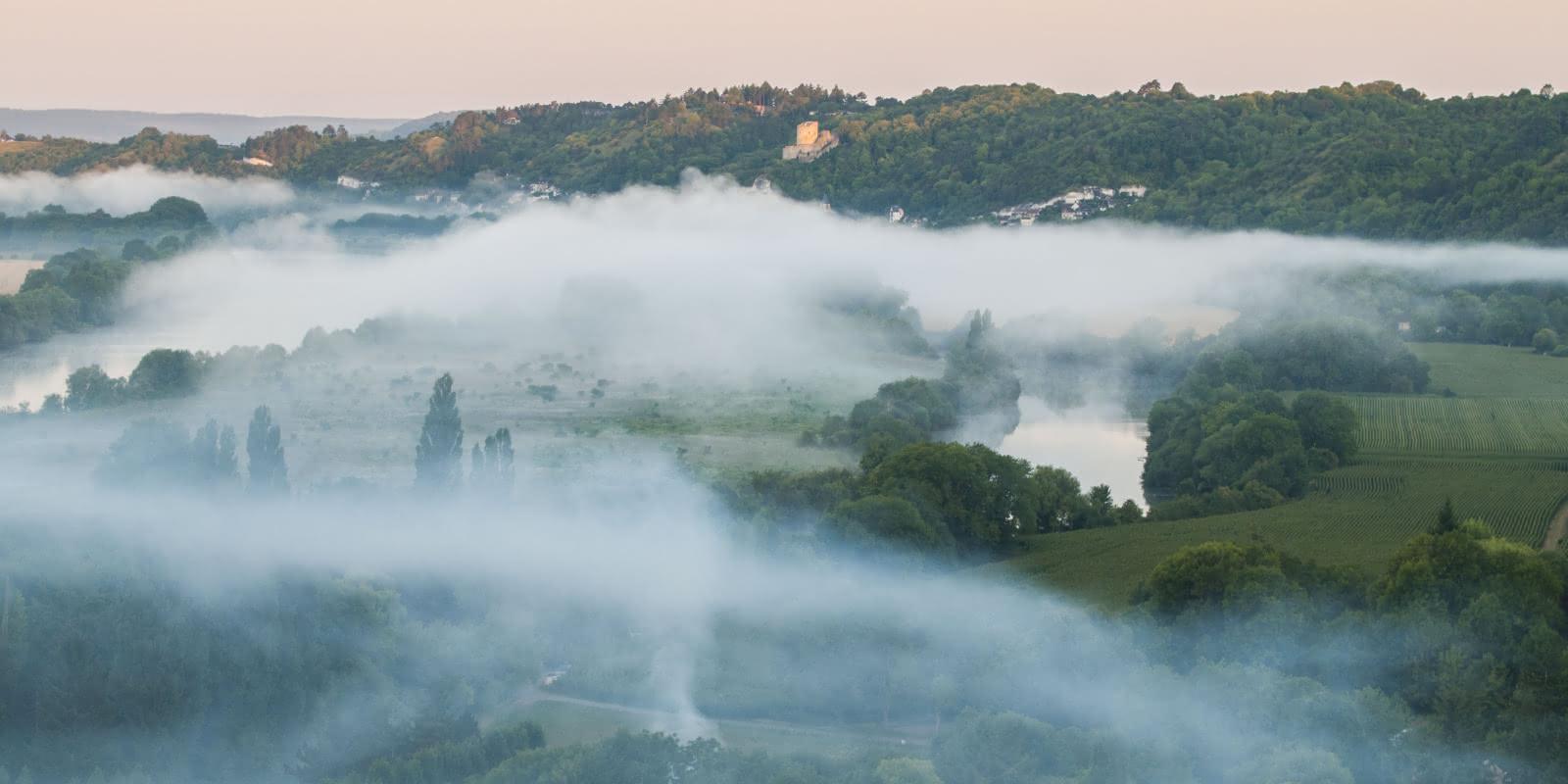 Photo de La Roche Guyon et de ses environs prise depuis une montgolfière avec une brume épaisse et blanche