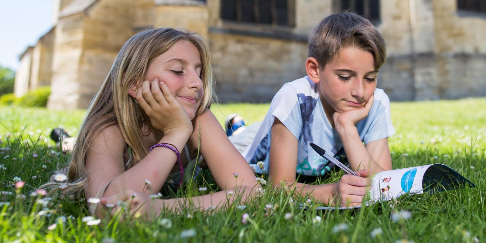 Photo de deux enfants dessinant sur un carnet de visite allongés dans l'herbe devant l'église d'Auvers sur Oise dans le Val d'Oise