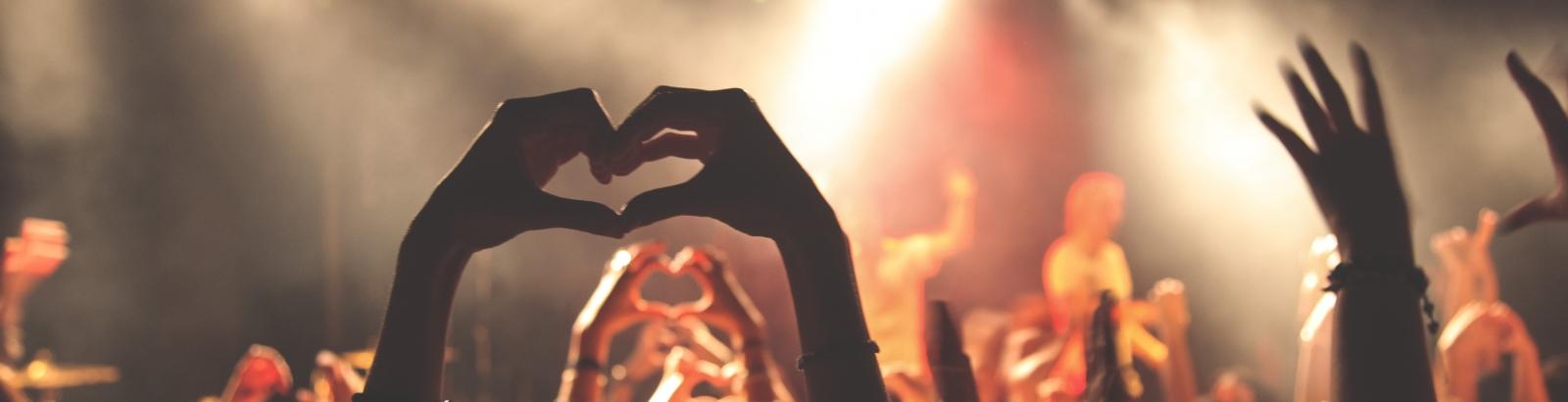 Mains formant un cœur à un concert