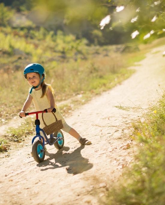 Photo d'une petite fille avec un casque sur un vélo pour enfant
