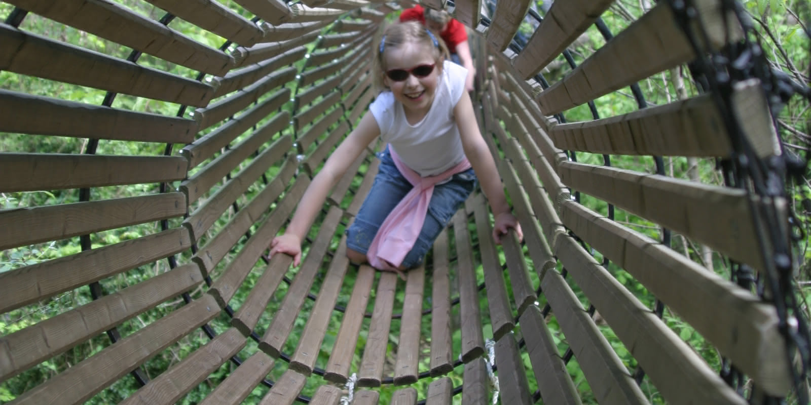 Photo d'une petite fille qui avance dans un tunnel en bois perché dans les arbres dans le parc de loisirs Aventure Land à Magny en Vexin dans le Val d'Oise