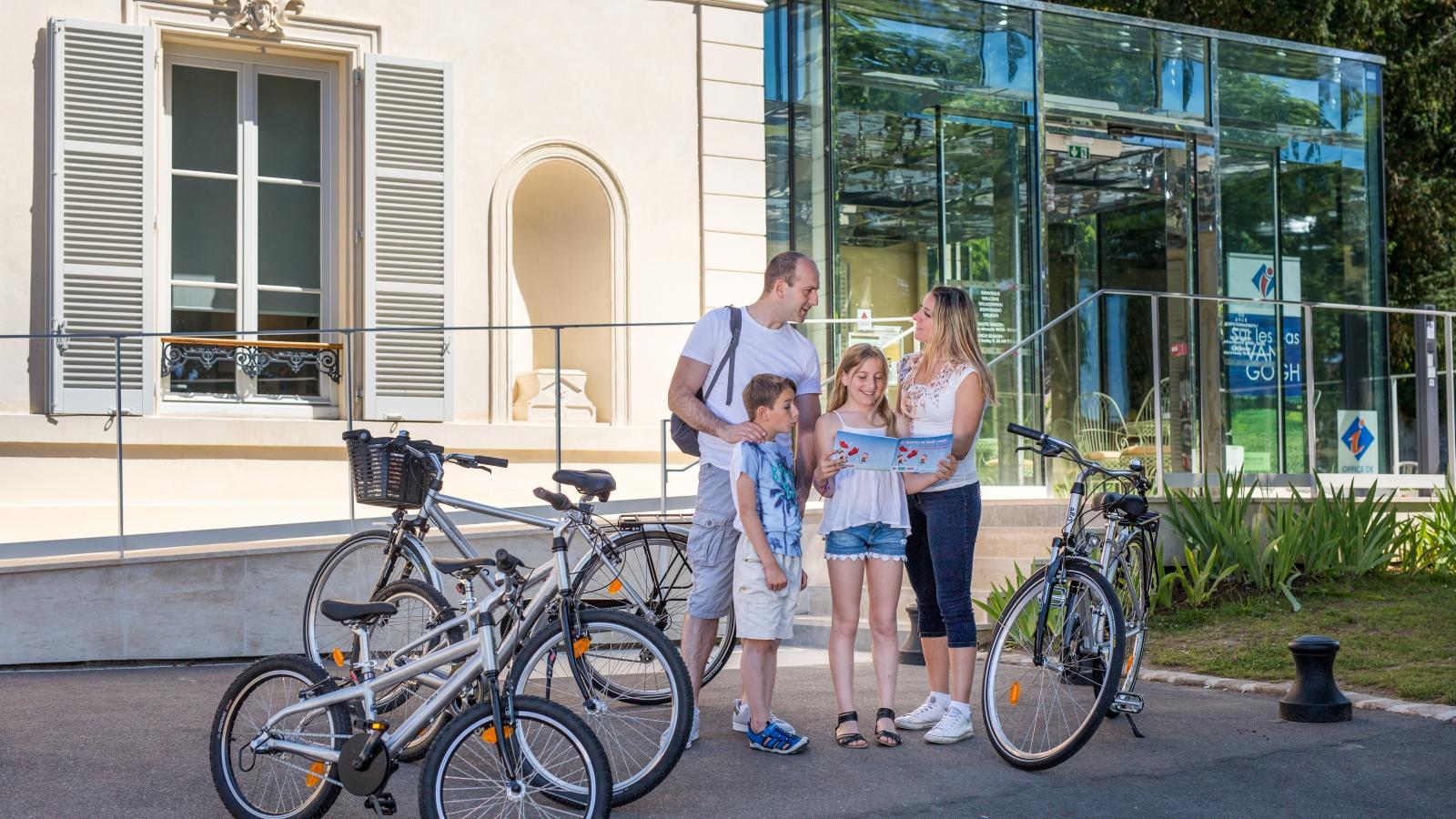 Photo d'une famille devant l'office de tourisme d'Auvers sur Oise regardant des plans et livrets de visite avec leur vélo près d'eux