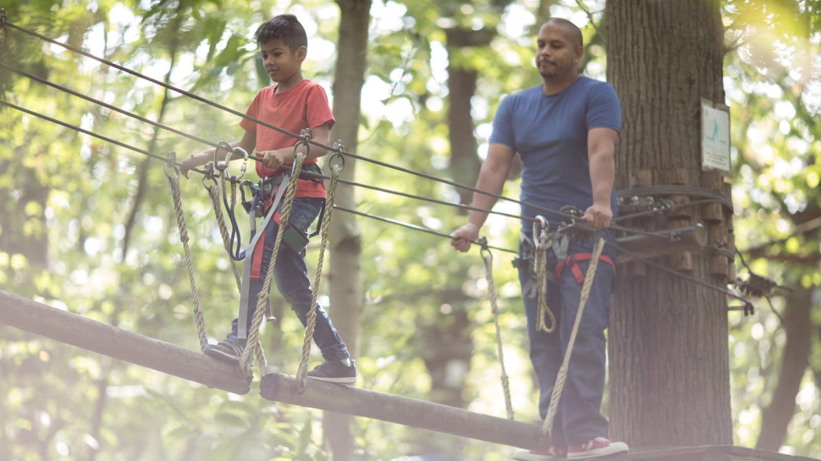 Photo d'un jeune garçon au t shirt rouge avec son papa sur un parcours d'accrobranche au parc Sherwood Parc dans le Val d'Oise