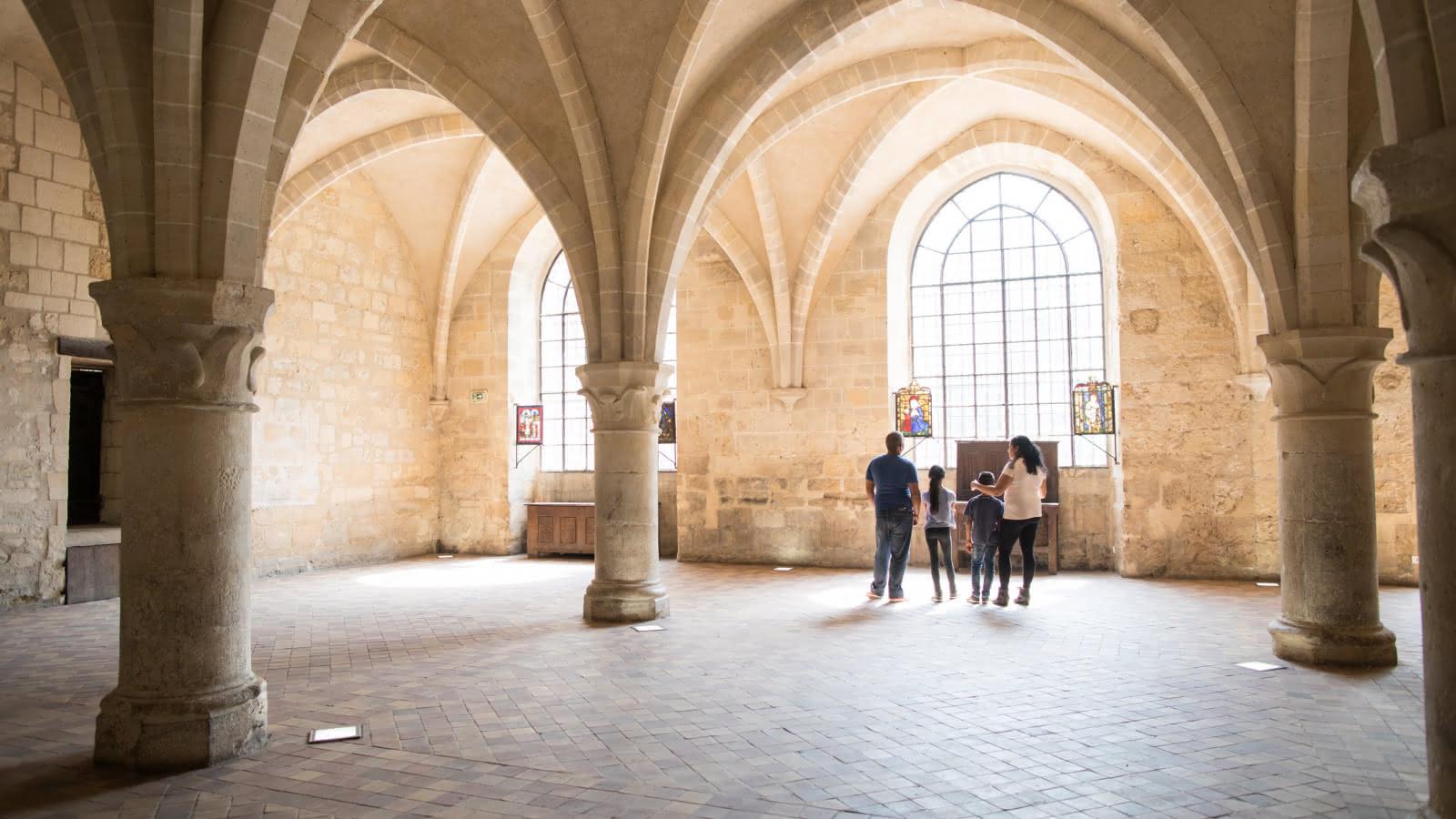 Photo d'une famille de deux parents et deux enfants qui observent les vitraux
