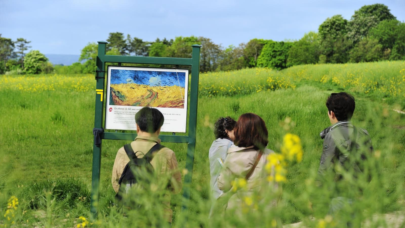 Auvers-sur-Oise, touriste chinois sur le chemin des Impressionnistes, devant les pancartes des peintures de Van Gogh se trouvant sur le parcours. Auvers-sur-Oise 2015.
