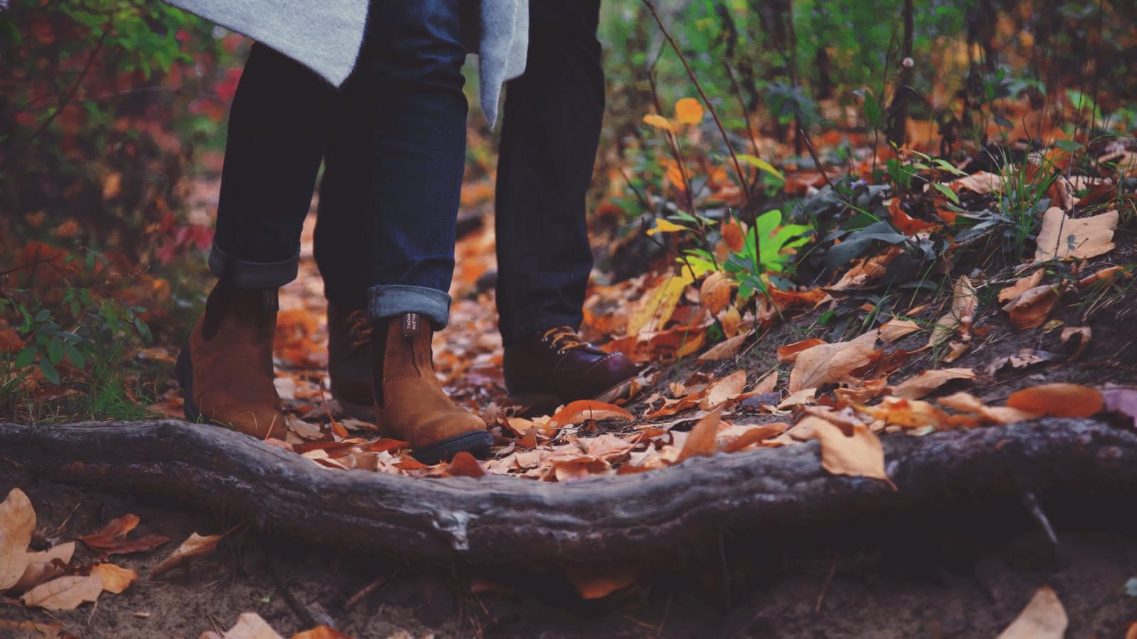 Photo d'un couple qui marche en forêt et dont on ne voit que les pieds.