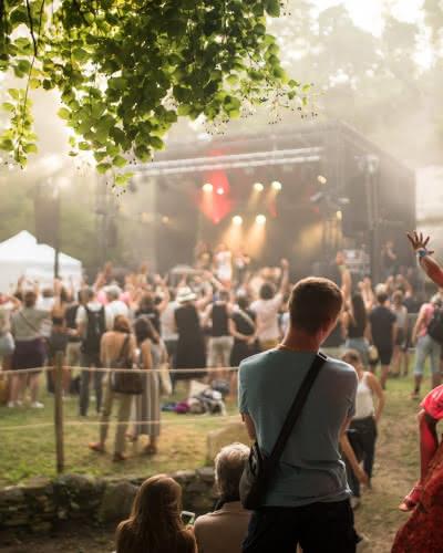 Photo d'une famille de dos regardant la scène d'un concert lors d'un festival