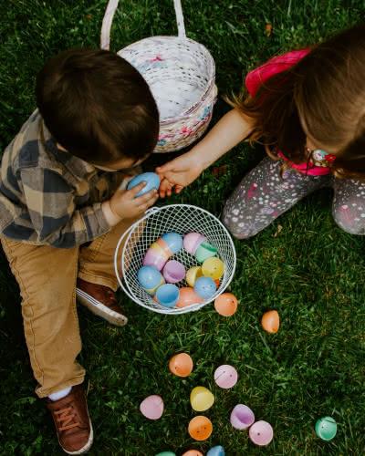 Deux enfants assis dans l'herbe avec des paniers d'œufs en chocolat de Pâques