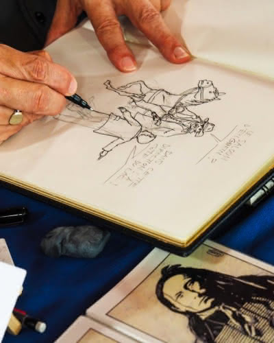 Photo zoomant sur la main du personne en train de réaliser un dessin sur un carnet de croquis
