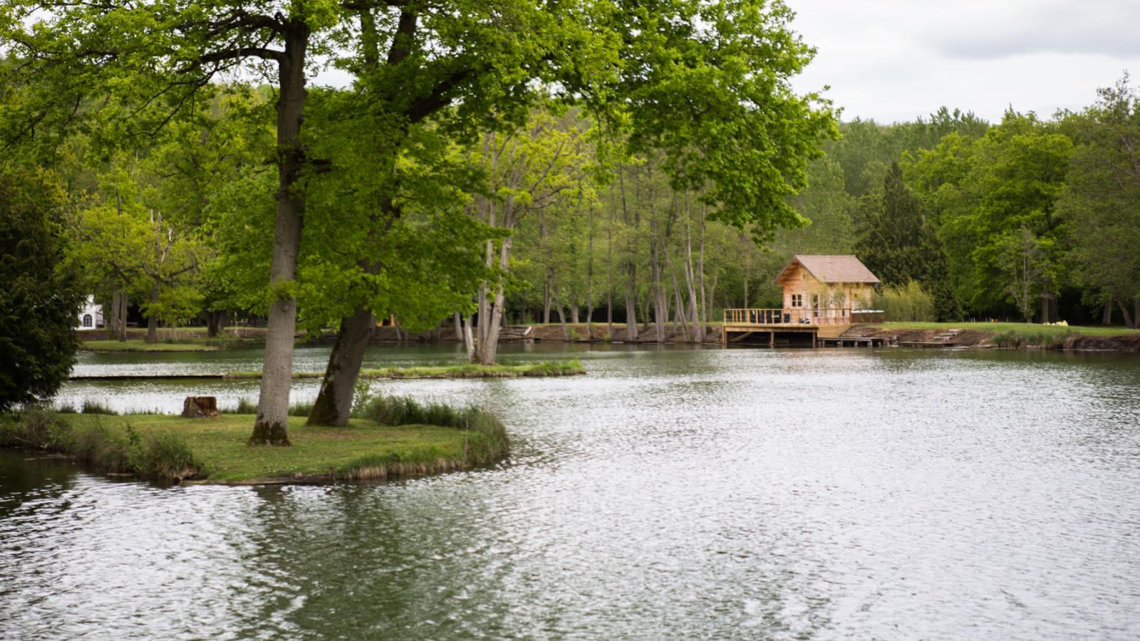 Photo montrant un des chalets des Etangs de la Palombière et un de ses lacs à Montreuil-sur-Epte dans le Vexin français