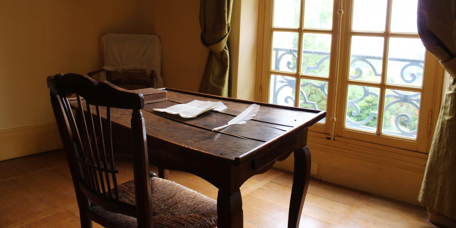 Photo de la chambre de Jean Jacques Rousseau avec son portrait au mur et son bureau