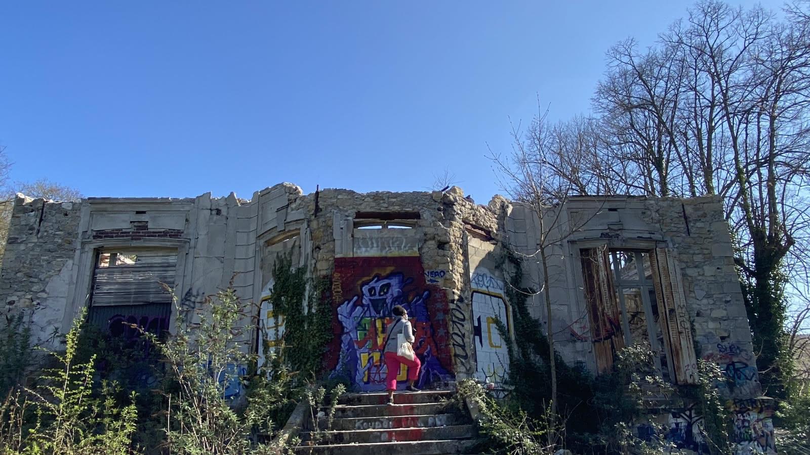 Femme de dos, montant les marches d'une ruine dont la façade est recouverte de graffitis à Goussainville