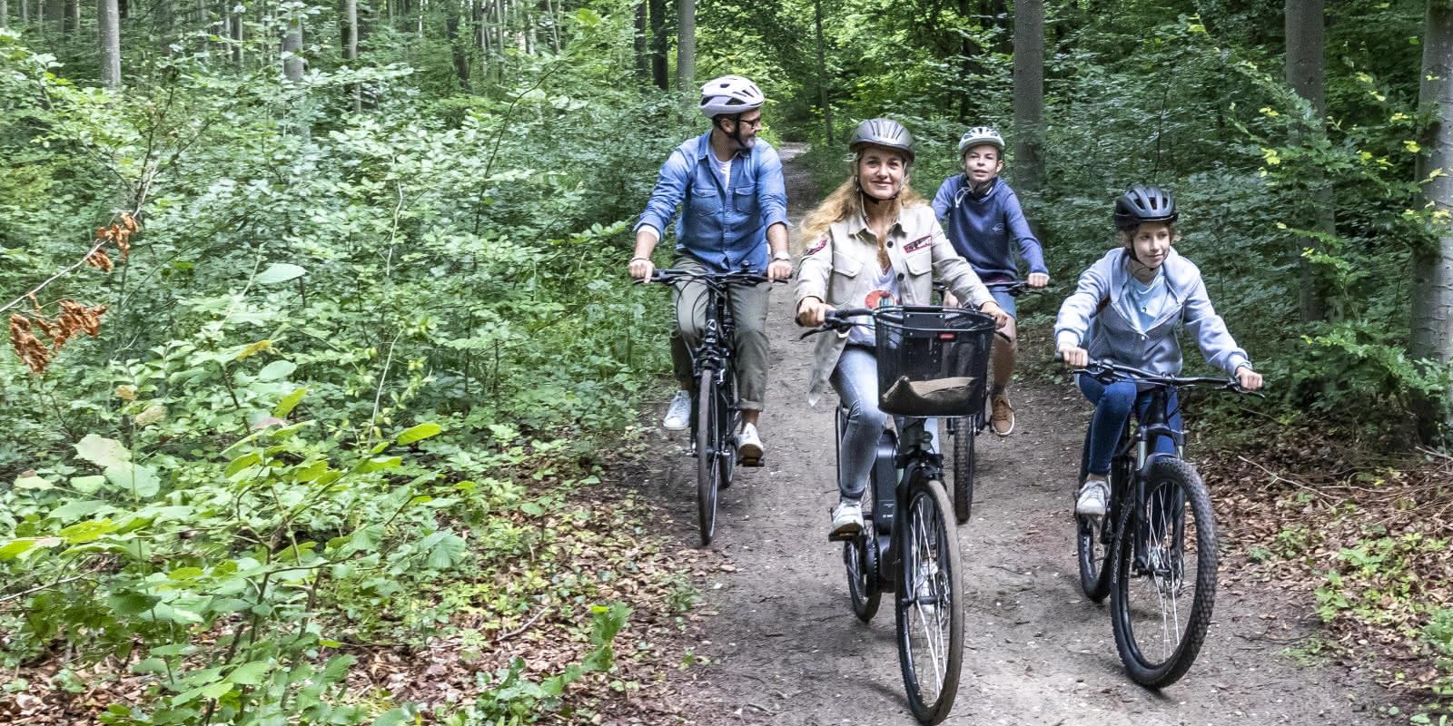 Famille en balade à vélo dans la forêt