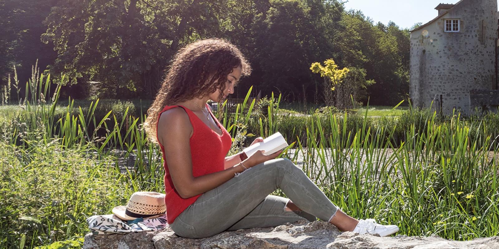 jeune femme avec un livre assise sur un muret devant le Château de la Chasse en arrière plan