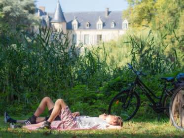 Photo de deux cyclistes allongés dans l'herbe du parc de la Maison du Parc à Théméricourt dans le Vexin