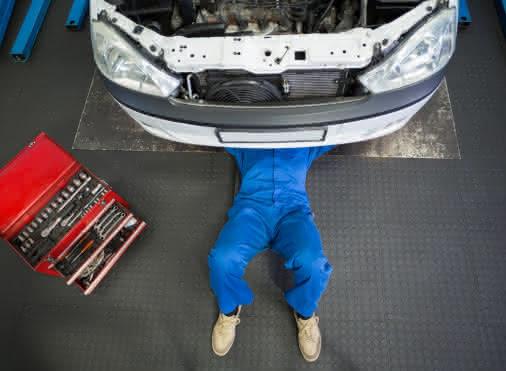 garagiste en train de réparer sous le chassis