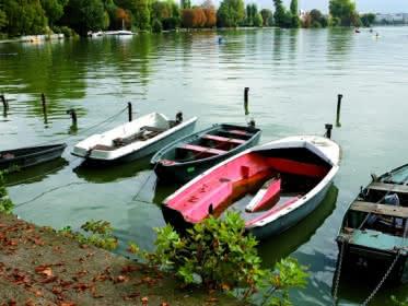 Photo d'une rangée de petites barques de multiples couleurs accrochées à un quai sur les bords du lac d'Enghien les Bains dans le Val d'Oise