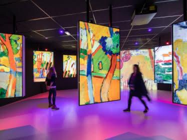 Photo d'une des salles du parcours de visite Vision Impressionniste du château d'Auvers sur Oise montrant des tableaux aux couleurs vives sous une lumière rose et rouge, avec des visiteurs les contemplant