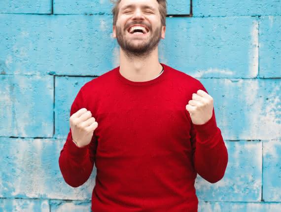 Photo d'un homme heureux à pull rouge devant un mur bleu heureux