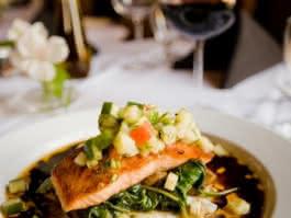 Photo d'un plat appétissant à base de saumon et légumes dans une assiette blanche avec plusieurs verres de vin en arrière plan
