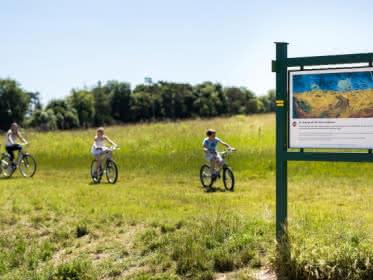 Photo d'une famille faisant du vélo près du champ de blé aux corbeaux peint par le peintre Vincent Van Gogh à Auvers sur Oise, avec un panneau explicatif au premier plan