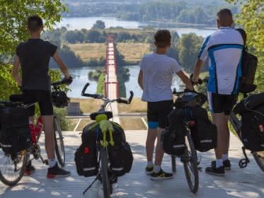 Photo d'un père et ses deux fils avec leur vélo regardant l'Axe majeur et sa passerelle qui s'offre à eux