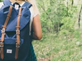 Photo d'une femme blonde portant un sac à dos bleu marine et une chemise à carreaux en train de randonner dans la forêt